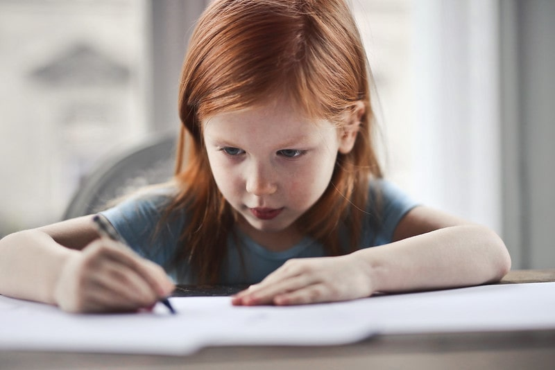 Young girl with red hair writing spelling on paper.