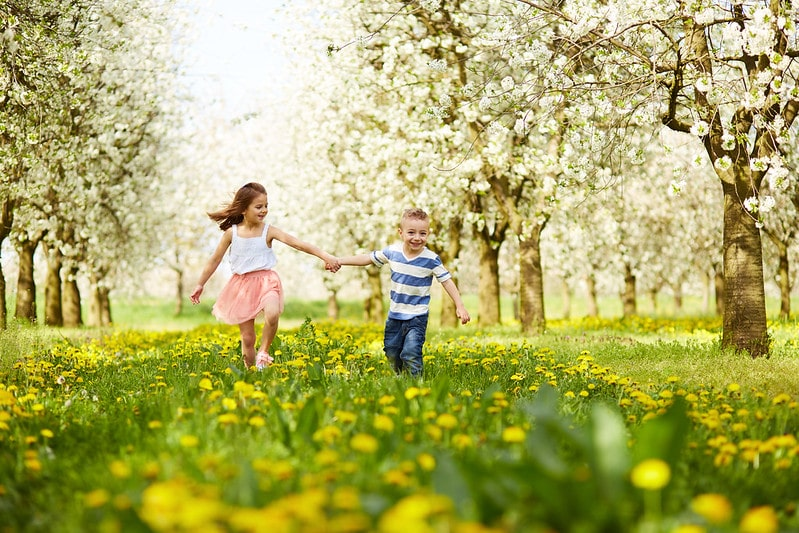 A boy and girl running through Swanley Park holding hands