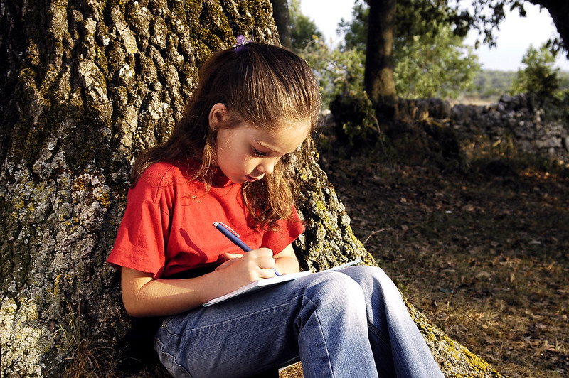 A girl writing in her diary outdoors
