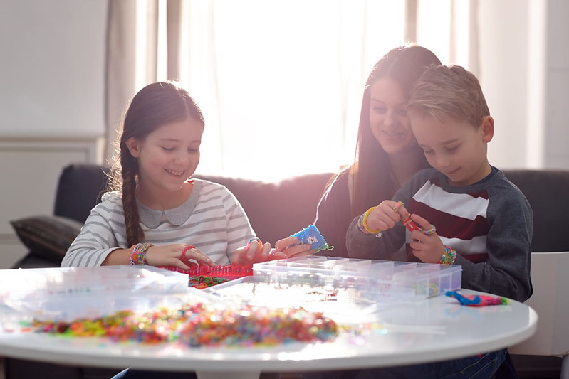 Mother and Two Children Playing With Loom Bands