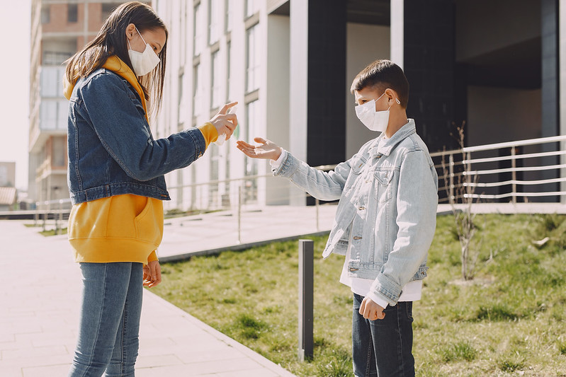 Boy and girl wearing masks spraying hand sanitiser