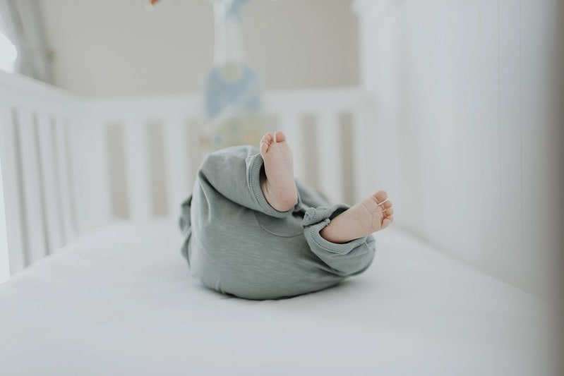 Baby in a crib with its feet in the air.
