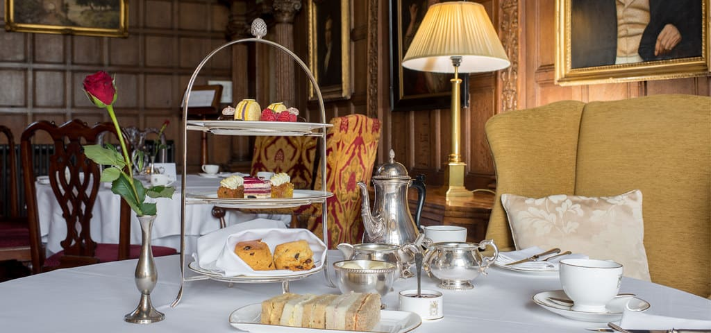Luxury afternoon tea with fancy silverware and plush furniture at Rushton Hall.