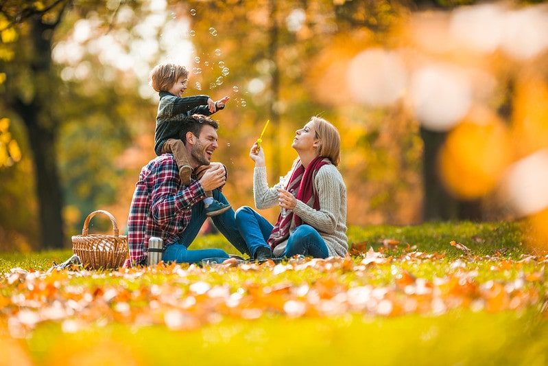 Family in Adventure Valley park in autumn blowing bubbles