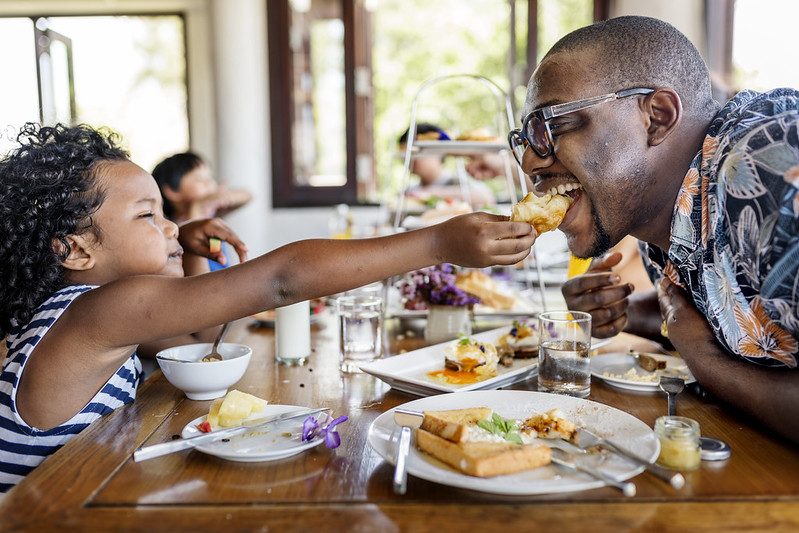 Young child attempting to playfully feed smiling man at the dinner table of a family restaurant.