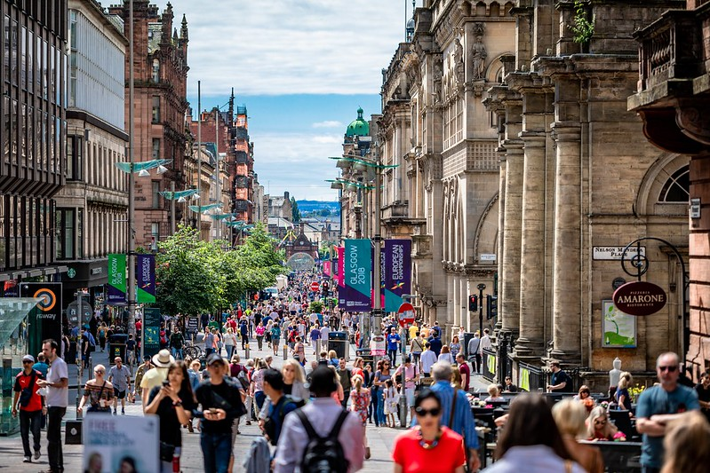 A busy high street in Glasgow, packed with shoppers.