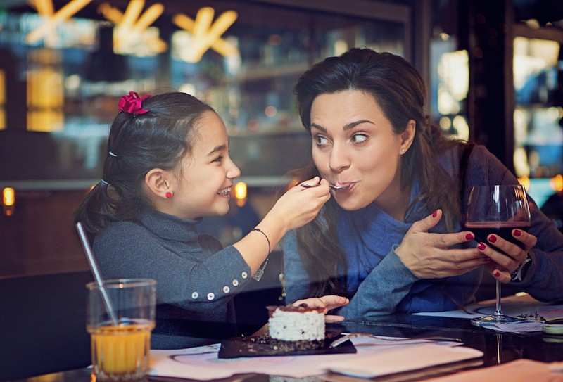 A young girl is feeding her mother cake at a restaurant.