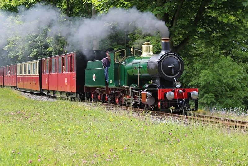 Colourful steam train moving along at Kirklees Light Railway.