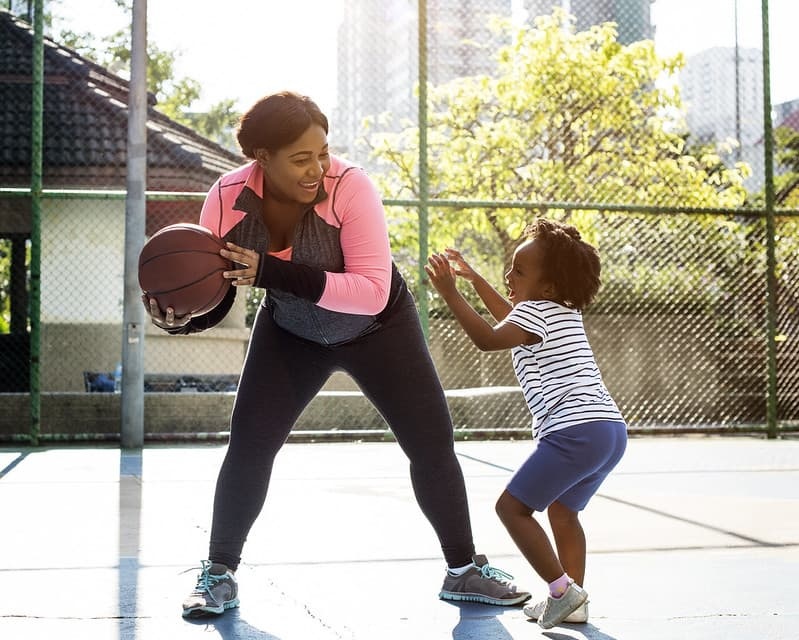 Mother and daughter smiling at each other while playing basketball.