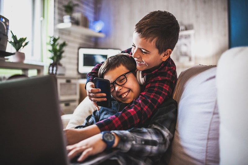 Two boys laughing while using gadgets on the sofa.