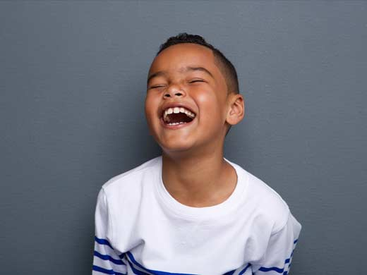 Young boy laughing at a joke.