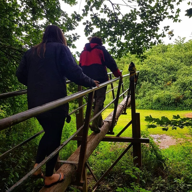 Two people crossing a bridge at Manley Mere