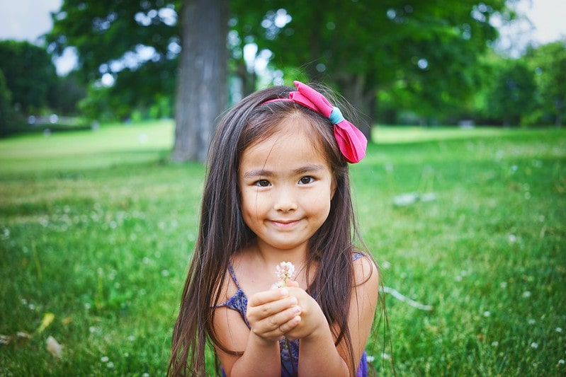 Little girl wearing a bow in her hair smiling and holding a flower.