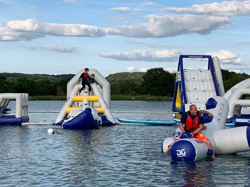 Family using the inflatable aqua park at Manley Mere