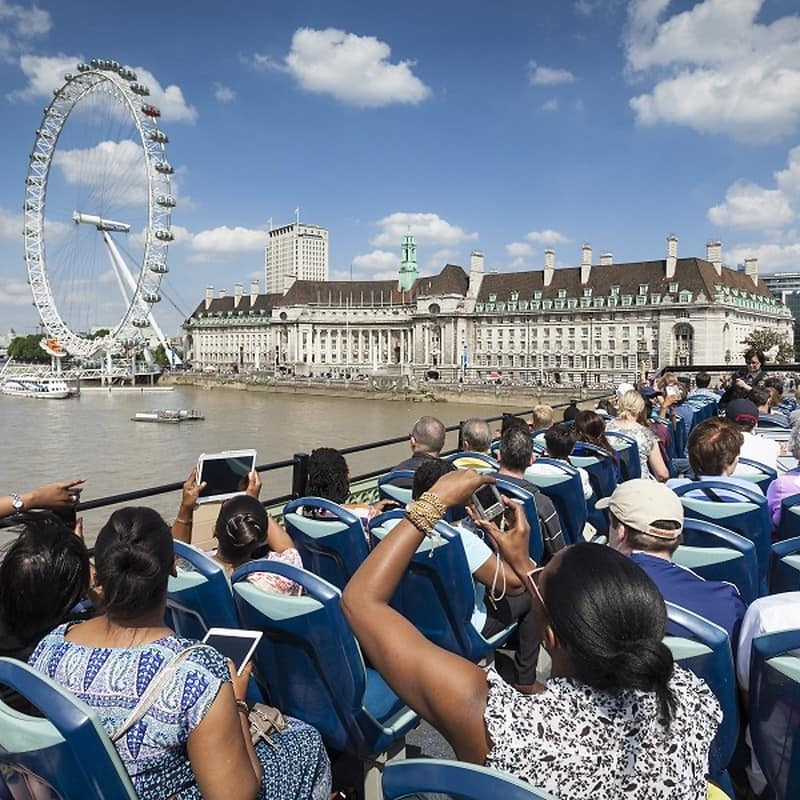 Hop-on, hop-off bus and boat tour group looking at the London Eye on their tour.