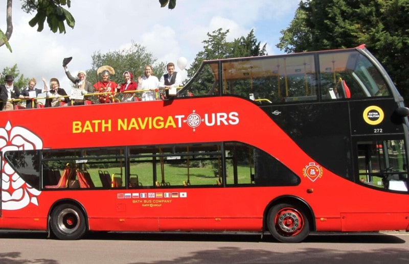 People stood up on the top deck of a sightseeing tour bus in Bath.