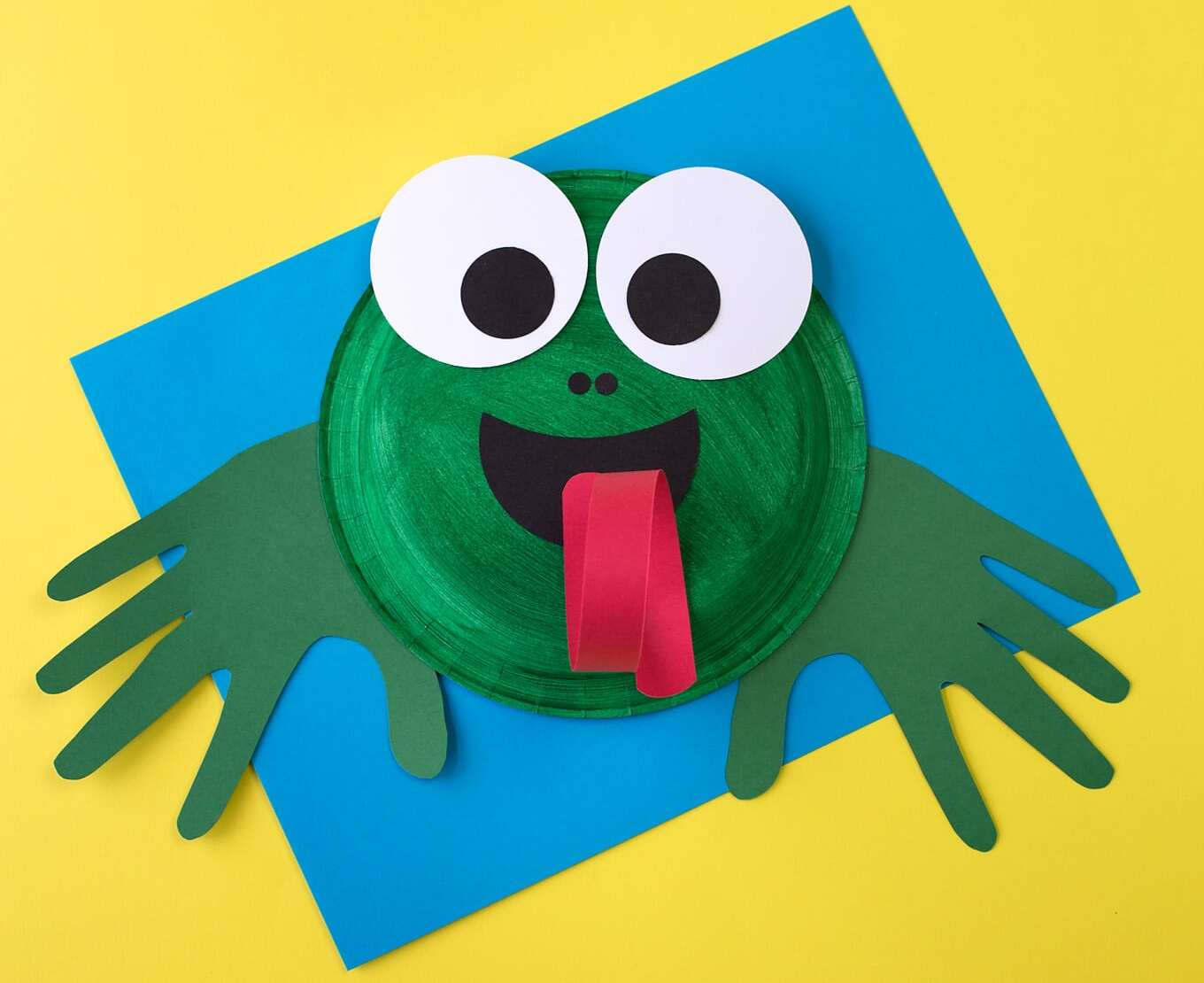 Paper plate frog face with big googly eyes and its tongue sticking out.