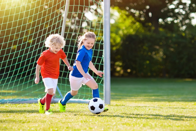 Little boy and girl playing football together and smiling.