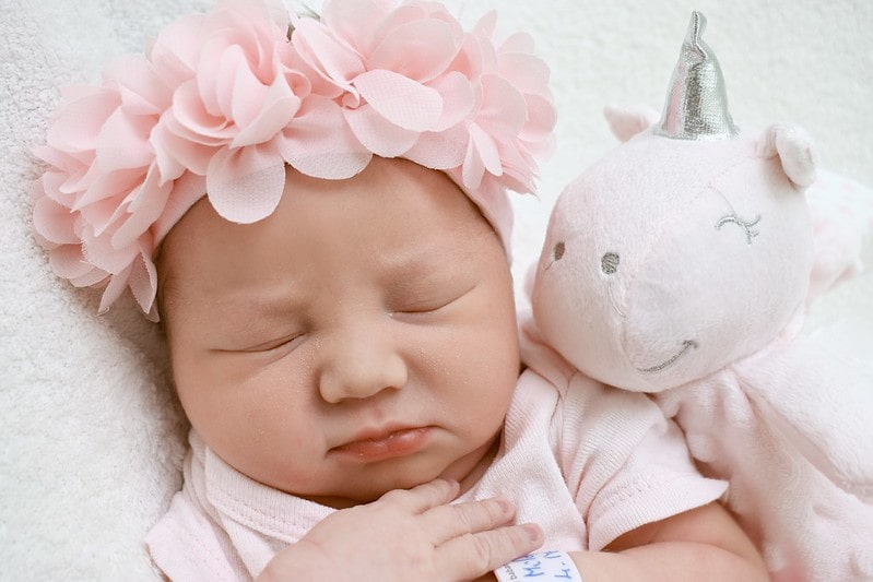 Newborn baby girl wearing a pink flower crown fast asleep next to a toy unicorn.