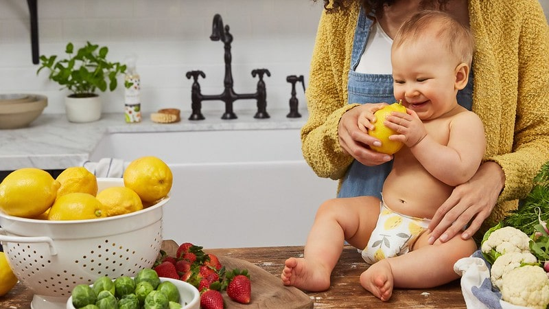 Baby sat on the kitchen worktop holding a lemon and smiling.