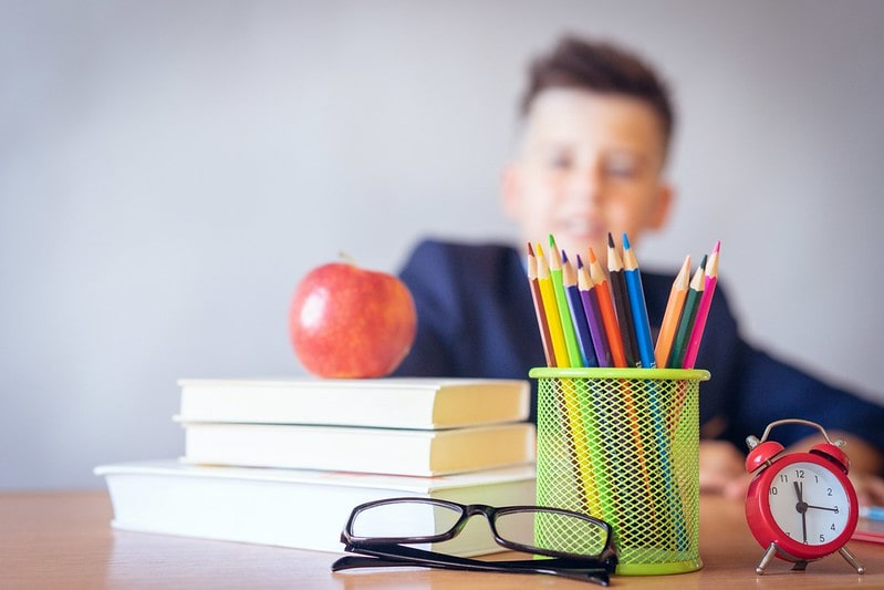 Boy sitting at school desk with book and colouring pencils.