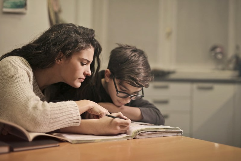 Mum helps her son study.