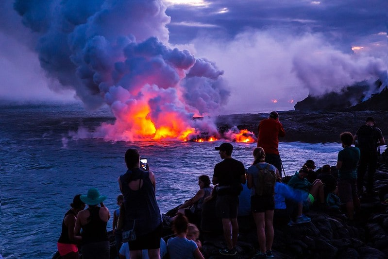 Onlookers watch as lava falls on the water after an eruption.