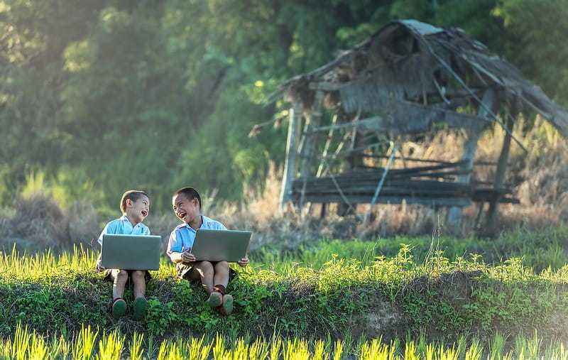 Two young boys sat outside with laptops looking at each other laughing.