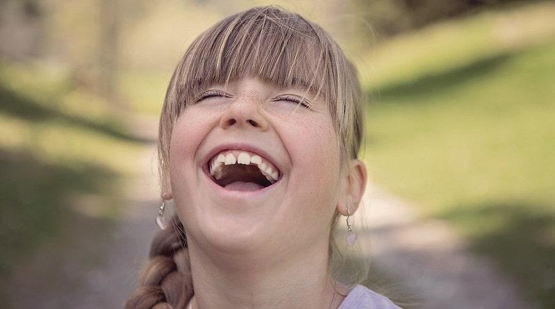Girl wearing earrings laughing at a joke.
