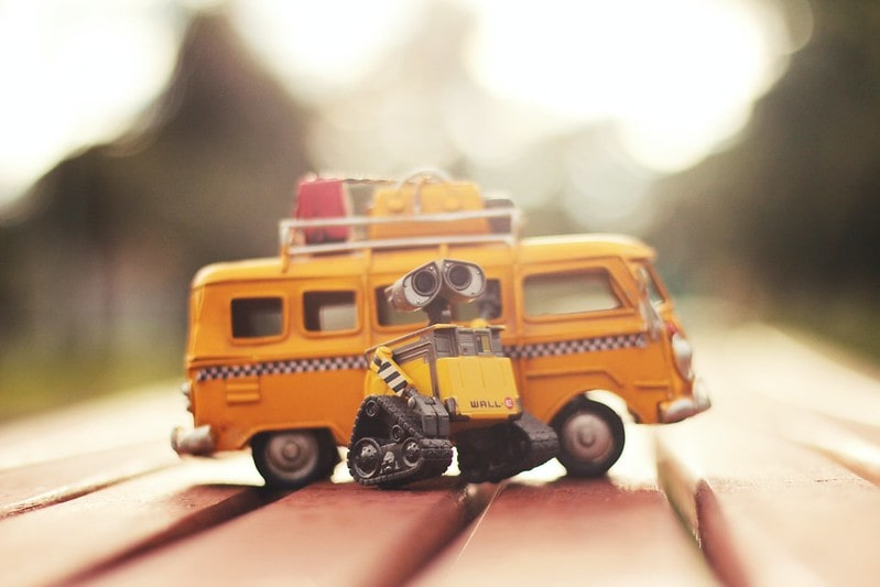 Yellow Wall-E robot toy next to a yellow school bus toy.