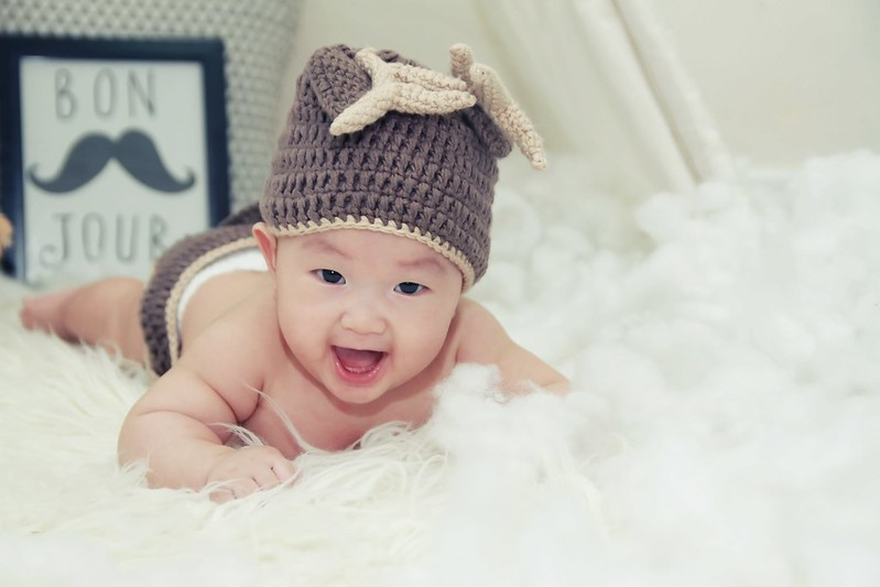 Smiling baby on white blanket wearing knitted hat.
