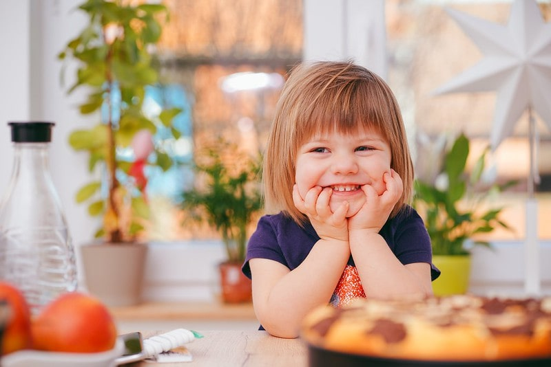Little girl sat at the kitchen table smiling at cooking jokes.