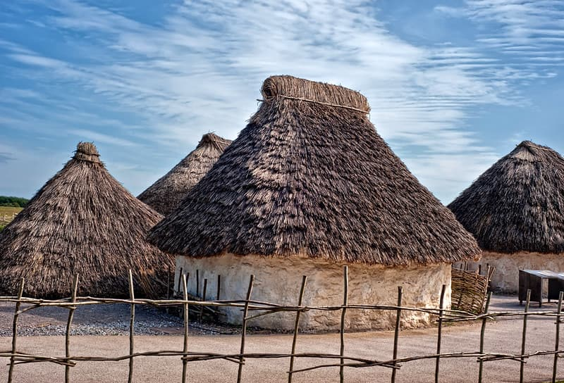 Circular Neolithic huts with thatched, pointed roofs on a sunny day