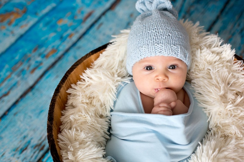 Baby born wearing blue woolly hat wrapped in blue on a fluffy blanket.