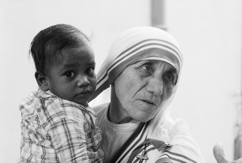 Mother Teresa holding a young boy in her arms.