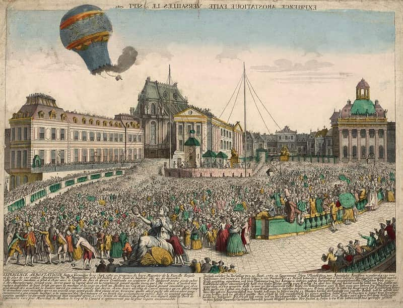 Old image of a hot air balloon gone wrong, burning above the crowd.