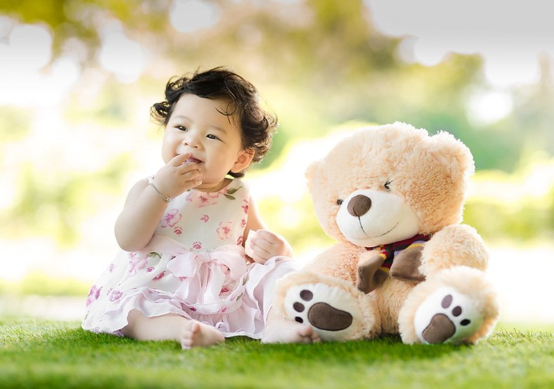 Baby girl in floral dress sat on the grass smiling next to her teddy bear.