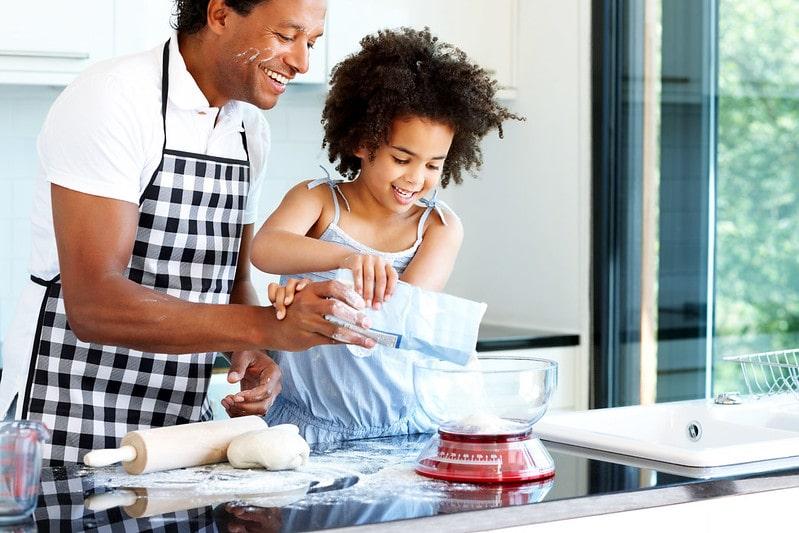 Dad Helping Daughter Bake Cake.