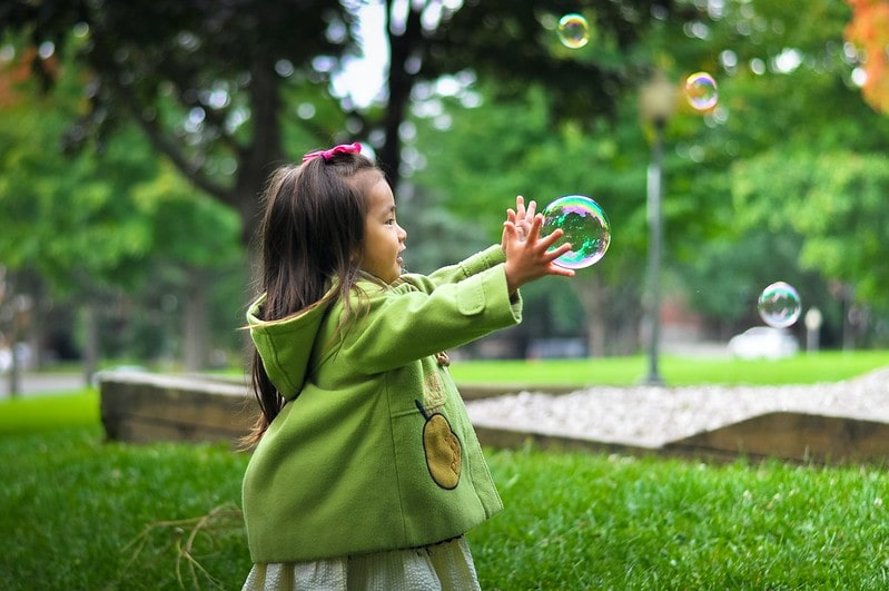 Little girl wearing a green jacket in the park reaching out to catch a bubble.