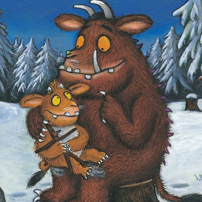 An adult Gruffalo sat on a tree stump in a snowy forest, with a young Gruffalo on his lap.