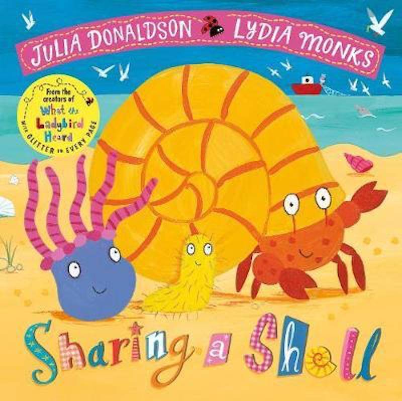 Cover of Sharing A Shell: two sea creatures and a red crab stand on the beach smiling. There is a large shell on the red crab's head and the ocean is in the background.