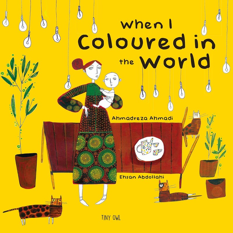 Cover of When I Coloured In The World: a woman in patterned green and brown clothing is holding a baby at her hip, both of which have no colour on their bodies. They are in a yellow room with brown furniture and three brown cats.