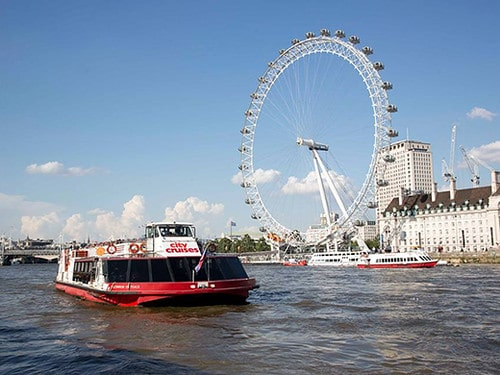 A city cruises boat on a tour, with the London Eye behind it.
