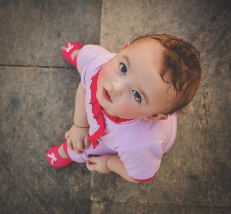 Baby girl wearing a pink outfit and pink shoes looking up at the camera.