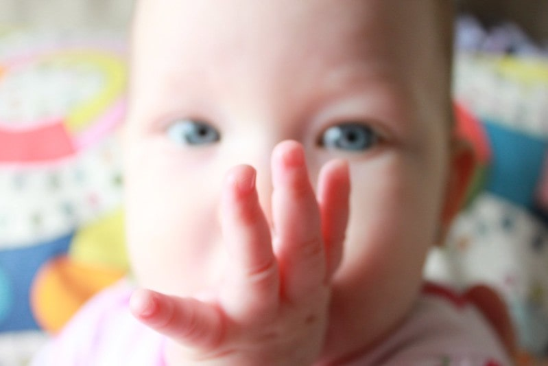 Blue-eyed baby with its thumb in its mouth.
