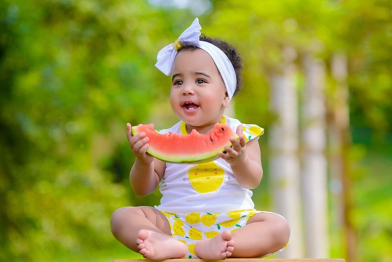 Toddler wearing a bow headband eating a piece of watermelon.