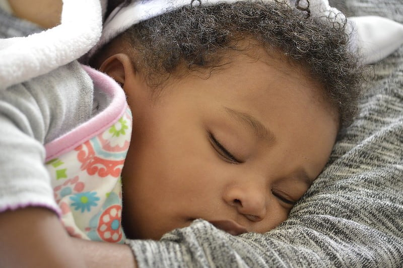 Baby girl sleeping in her mum's arms without a dummy.