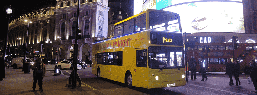 The yellow See London By Night Bus Tour driving past Piccadilly Circus.