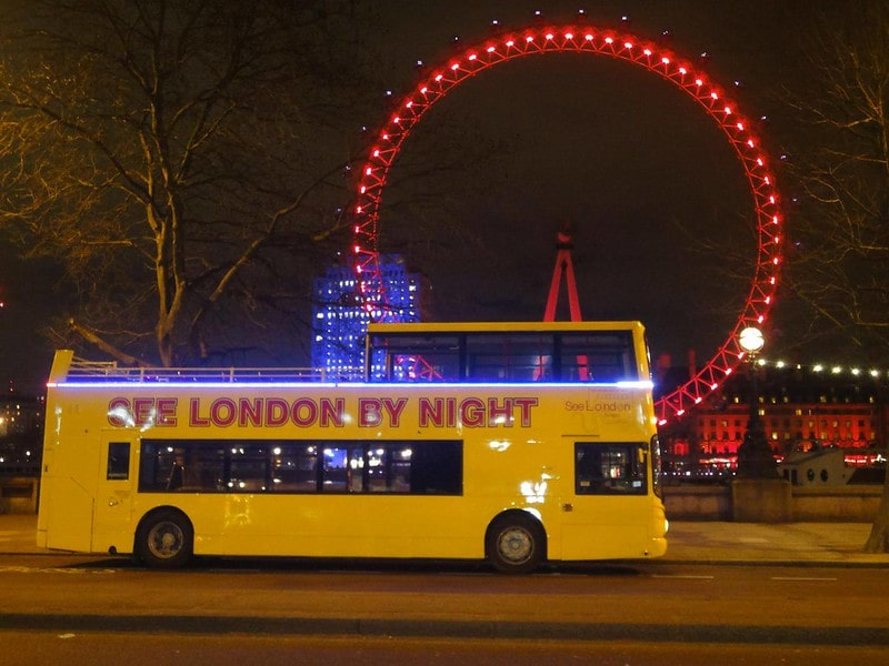 A yellow See London By Night Bus Tour driving past the London Eye.