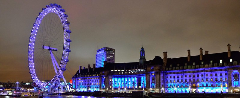 A view from Westminster Bridge of the London Eye lit up at night.